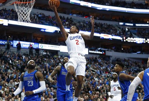 LA Clippers guard Shai Gilgeous-Alexander (2) drives to the basket against Dallas Mavericks defenders Wesley Matthews (23), DeAndre Jordan, back, and Dennis Smith Jr. (1) during the first half of an NBA basketball game in Dallas, Tuesday, Jan. 22, 2019.