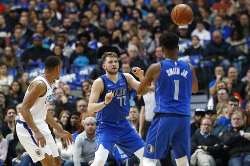 Dallas Mavericks guard Dennis Smith Jr. (1) passes to Dallas Mavericks forward Luka Doncic (77) of Germany against LA Clippers guard Avery Bradley during the first half of an NBA basketball game in Dallas, Tuesday, Jan. 22, 2019.