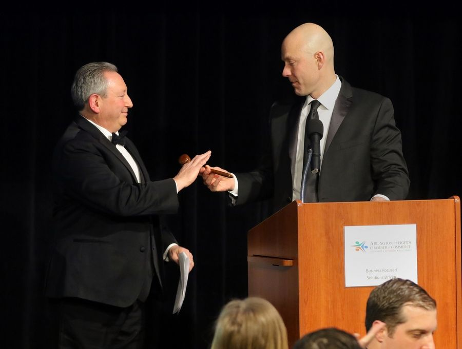 Outgoing Arlington Heights Chamber of Commerce Chairman Jason Miller, right, hands the gavel to incoming Chairman David Jaffe during the organization's 72nd annual awards and recognition gala Friday at Arlington International Racecourse.