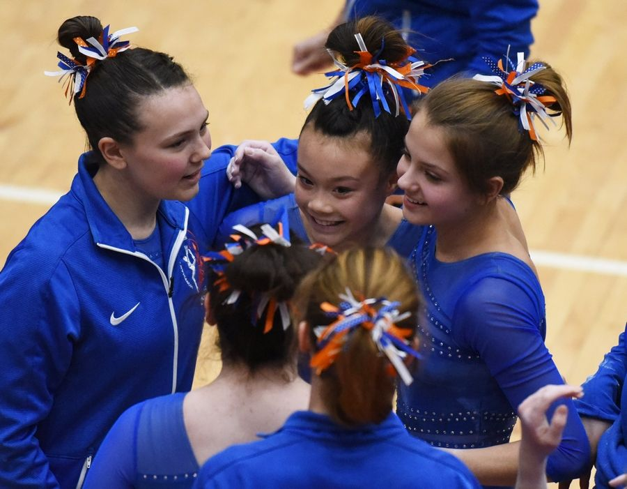 Hoffman Estates' Elyssa Wuerffel, center, gets hugs from teammates after her uneven parallel bar routine Monday at the Hoffman Estates regional gymnastics meet.