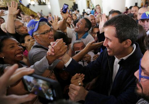 Opposition National Assembly leader Juan Guaido, right, who declared himself interim president, greets supporters as he leaves church after attending Mass in Caracas, Venezuela, Sunday, Jan. 27, 2019. Guaido says he is acting in accordance with two articles of the constitution that give the National Assembly president the right to hold power temporarily and call new elections.