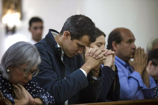 Opposition National Assembly President Juan Guaido, who declared himself interim president of Venezuela, prays next to his wife Fabiana Rosales, second from right, during Mass at a church in Caracas, Venezuela, Sunday, Jan. 27, 2019. Guaido says he is acting in accordance with two articles of the constitution that give the National Assembly president the right to hold power temporarily and call new elections.