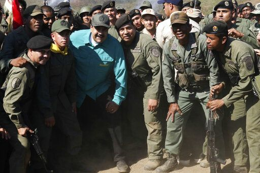 In this photo released to the media by Miraflores presidential palace press office, Venezuelan President Nicolas Maduro, wearing a blue shirt, third from left in the front row, poses for photos with soldiers as he visits Ft. Paramacay in Carabobo state, Venezuela, Sunday, Jan. 27, 2019. Opposition lawmaker Juan Guaido has declared himself Venezuela's legitimate leader, as embattled socialist Maduro holds the reins of power. (Marcelo Garcia/Miraflores presidential palace press office via AP)