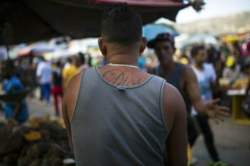 "A worker who has ""God"" tattooed on his back talks to a customer at his vegetables stand at a wholesale food market in Caracas, Venezuela, Monday, Jan. 28, 2019. Economists agree that the longer the standoff between the U.S.-backed opposition leader Juan Guaido and President Nicolas Maduro drags on, the more regular Venezuelans are likely to suffer."