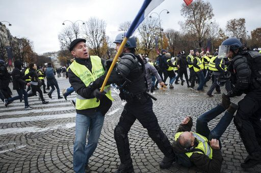 "FILE - In this Saturday, Nov. 24, 2018 file photo, Herve Ryssen, left, close to the ultra-right and convicted for antisemitic and racist comments, wearing a yellow jacket, clashes with riot police officers on the Champs-Elysees avenue in Paris. Intolerance and conspiracy theories have haunted the margins of France's ""yellow vest� movement since the first protests over fuel taxes roused the discontented middle of French society."
