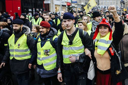 "FILE - In this Saturday, Jan. 5, 2019 file photo, Victor Lenta, a former soldier who fought alongside pro-Russian separatist forces in Ukraine, 2nd left with a red beret, demonstrates with yellow vest protesters during a march in Paris. Intolerance and conspiracy theories have haunted the margins of France's ""yellow vest� movement since the first protests over fuel taxes roused the discontented middle of French society."