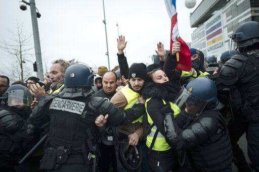 "FILE - In this Saturday, Dec. 29, 2018 file photo, French riot police officers hold back demonstrators wearing yellow vests as they demonstrate in front of the French public television network (France Televisions) in Paris. Intolerance and conspiracy theories have haunted the margins of France's ""yellow vest� movement since the first protests over fuel taxes roused the discontented middle of French society."