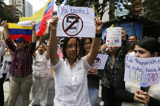 A woman holds a sign with a no symbol over an image representing President Nicolas Maduro in a walk out against Maduro, in Caracas, Venezuela, Wednesday, Jan. 30, 2019. Venezuelans are exiting their homes and workplaces in a walkout organized by the opposition to demand that Maduro leave power.