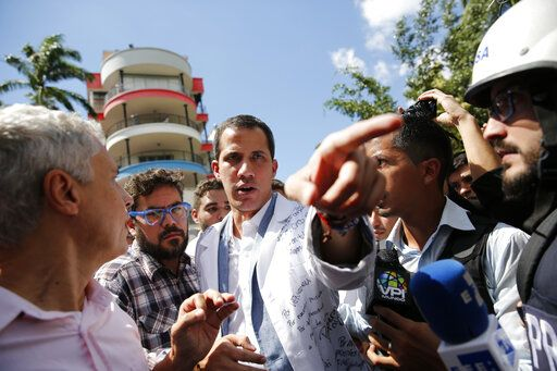 Opposition National Assembly President Juan Guaido, who declared himself interim president of Venezuela, speaks to reporters during a walk out against President Nicolas Maduro, in Caracas, Venezuela, Wednesday, Jan. 30, 2019. Venezuelans are exiting their homes and workplaces in a walkout organized by the opposition to demand that Maduro leave power.