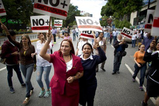 "People holding signs with a message that reads in Spanish: ""No more dictatorship"" take part in a walk out against President Nicolas Maduro, in Caracas, Venezuela, Wednesday, Jan. 30, 2019. Venezuelans are exiting their homes and workplaces in a walkout organized by the opposition to demand that Maduro leave power."