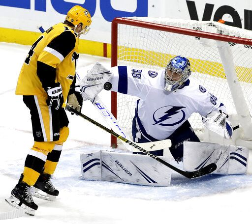 Tampa Bay Lightning goaltender Andrei Vasilevskiy (88) blocks a shot with Pittsburgh Penguins' Tanner Pearson (14) looking for the rebound during the first period of an NHL hockey game in Pittsburgh, Wednesday, Jan. 30, 2019.