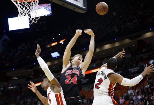 Chicago Bulls forward Lauri Markkanen (24) loses control of the ball as Miami Heat guard Josh Richardson, left, and guard Wayne Ellington (2) defend during the first half of an NBA basketball game, Wednesday, Jan. 30, 2019, in Miami.
