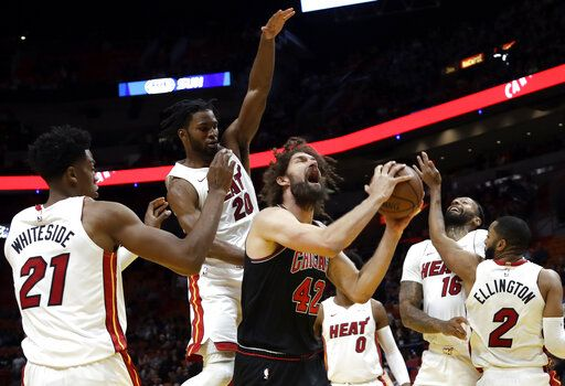 Chicago Bulls center Robin Lopez (42) is fouled by Miami Heat forward Justise Winslow (20) during the first half of an NBA basketball game, Wednesday, Jan. 30, 2019, in Miami.