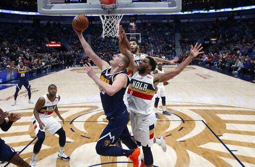 Denver Nuggets center Nikola Jokic (15) goes to the basket against New Orleans Pelicans center Jahlil Okafor (8) during the second half of an NBA basketball game in New Orleans, Wednesday, Jan. 30, 2019. The Nuggets won 105-99.