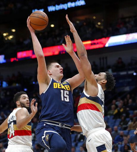 Denver Nuggets center Nikola Jokic (15) goes to the basket against New Orleans Pelicans center Jahlil Okafor in the first half of an NBA basketball game in New Orleans, Wednesday, Jan. 30, 2019.