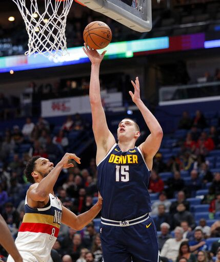 Denver Nuggets center Nikola Jokic (15) goes to the basket against New Orleans Pelicans center Jahlil Okafor during the first half of an NBA basketball game in New Orleans, Wednesday, Jan. 30, 2019.