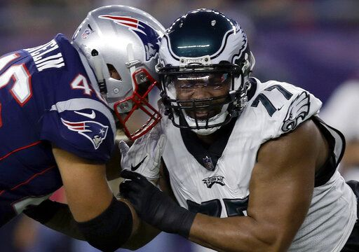 FILE- In this Aug. 16, 2018, file photo, Philadelphia Eagles defensive end Michael Bennett (77) tries to move past a block from New England Patriots fullback James Develin (46) during the first half of a preseason NFL football game in Foxborough, Mass. Develin is one of the few remaining true fullbacks in the NFL whose primary job is to just put his pads down and block.