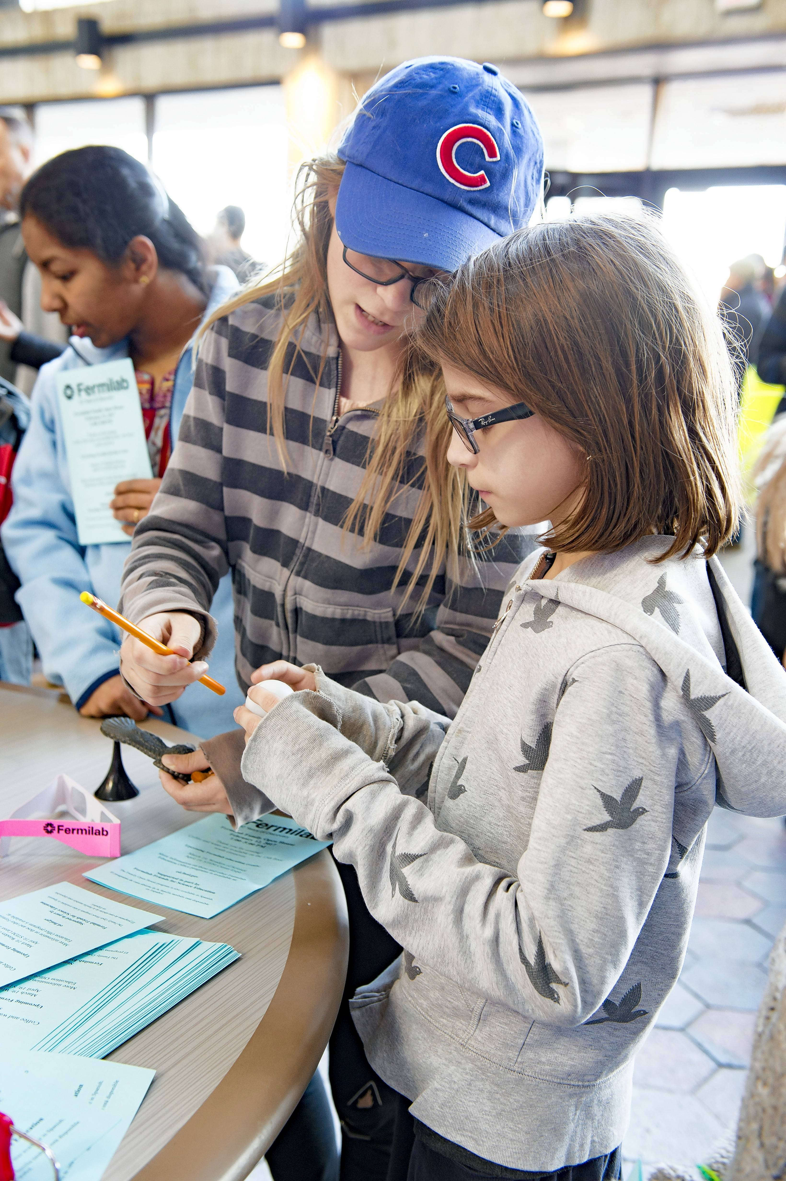 At Fermilab's Family Open House on Sunday, Feb. 10, families can work together to find the center of mass of various objects.
