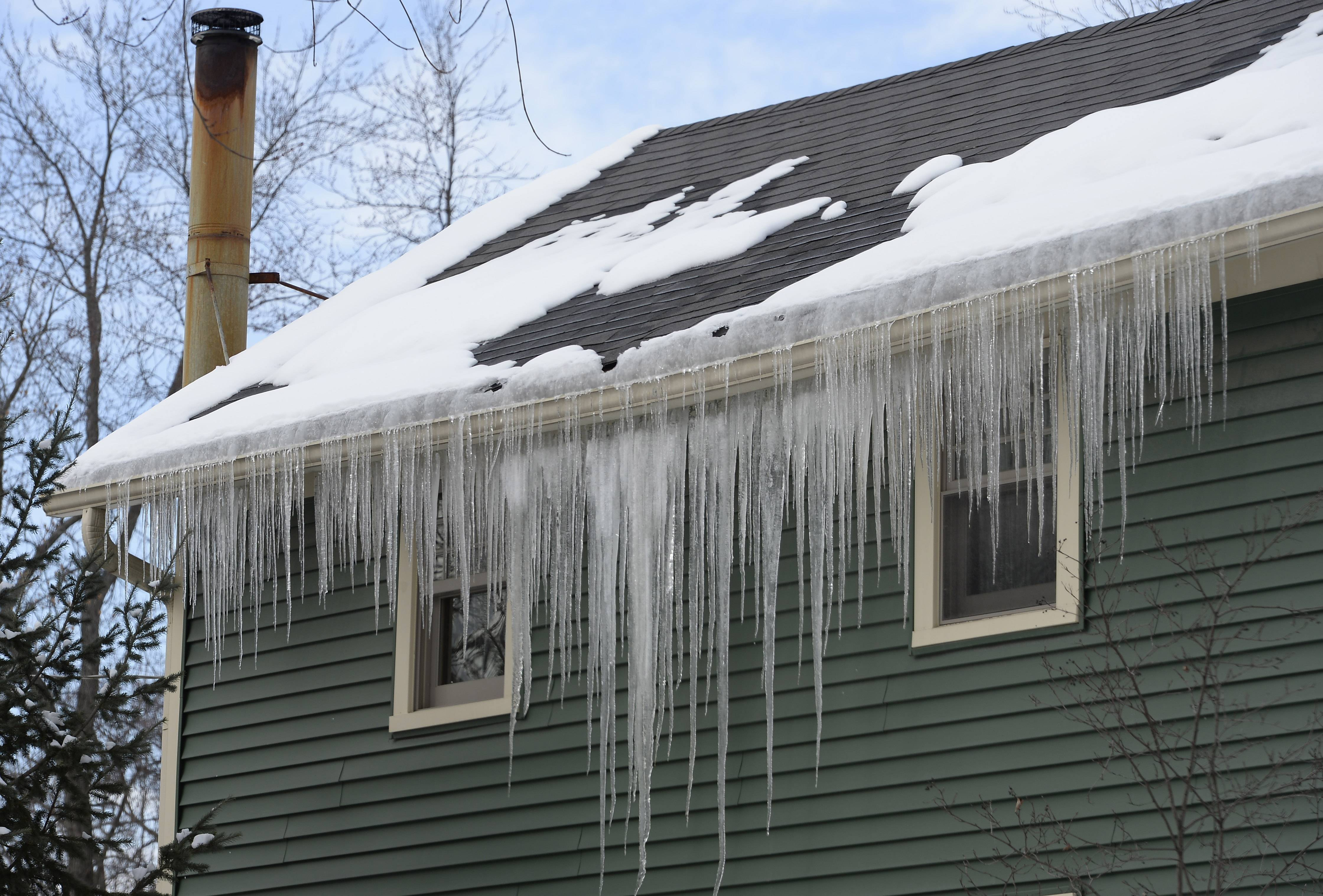 Icicles created by an ice dam last February hang from a house in Palatine. With the temperatures climbing in the next few days, ice dams could threaten many suburban homes' roofs.