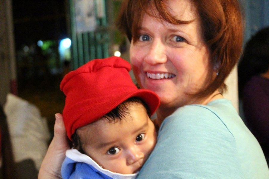 Kathleen O'Connor holds a patient while the mother receives dental treatment in rural Mexico.