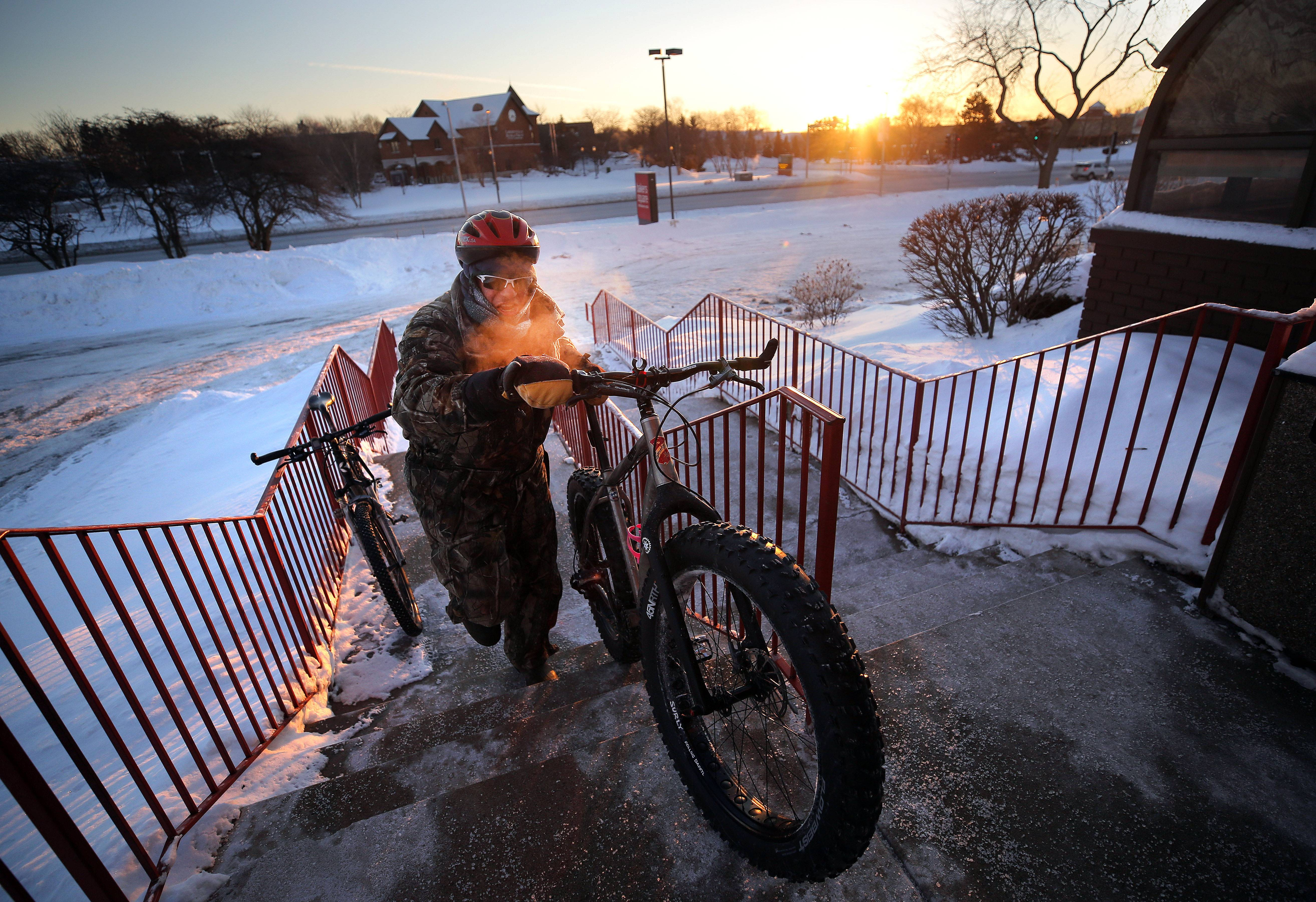 Peter Sherman, of Old Mill Creek pushes his bike up to the Bakers Square in Libertyville after a group ride as temperatures hovered around -20 Thursday morning in Lake County.
