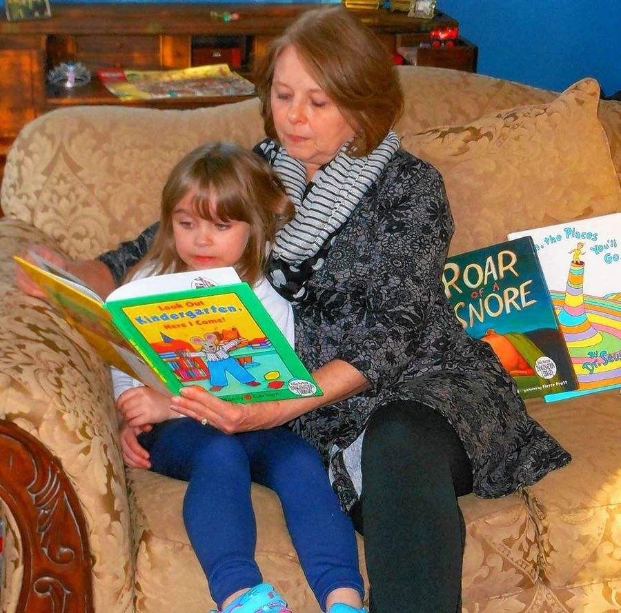 Former United Way of Elgin board member Judy Cabrera reads a book in Dolly Parton's Imagination Library program to her granddaughter, Cecilia, last year. The agency will end its 10-year program participation in June.