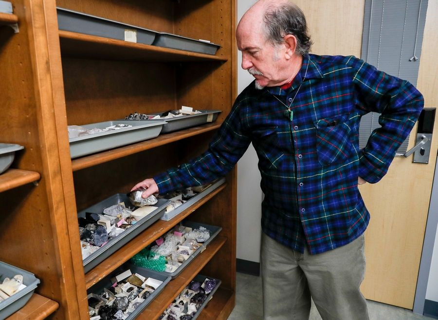 Jeff Greenberg, professor emeritus of geology at Wheaton College, inspects some of the mineral rocks that will be for sale.
