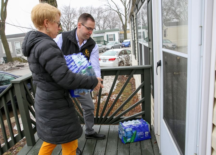 Elk Grove High School Associate Principal Kyle Burritt and Math and Science Division Head Mary Kemp drop off bottled water to a home in the Blackhawk Estates mobile home park in unincorporated Elk Grove Township on Wednesday. Some residents say they have been without clean water for a week and a half.