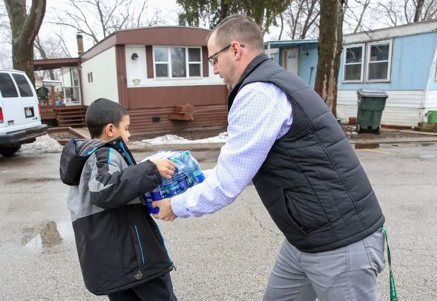 Elk Grove High School Associate Principal Kyle Burritt hands a case of bottled water to Anthony Hall, 11, on Wednesday afternoon in the Blackhawk Estates mobile home park in unincorporated Elk Grove Township.