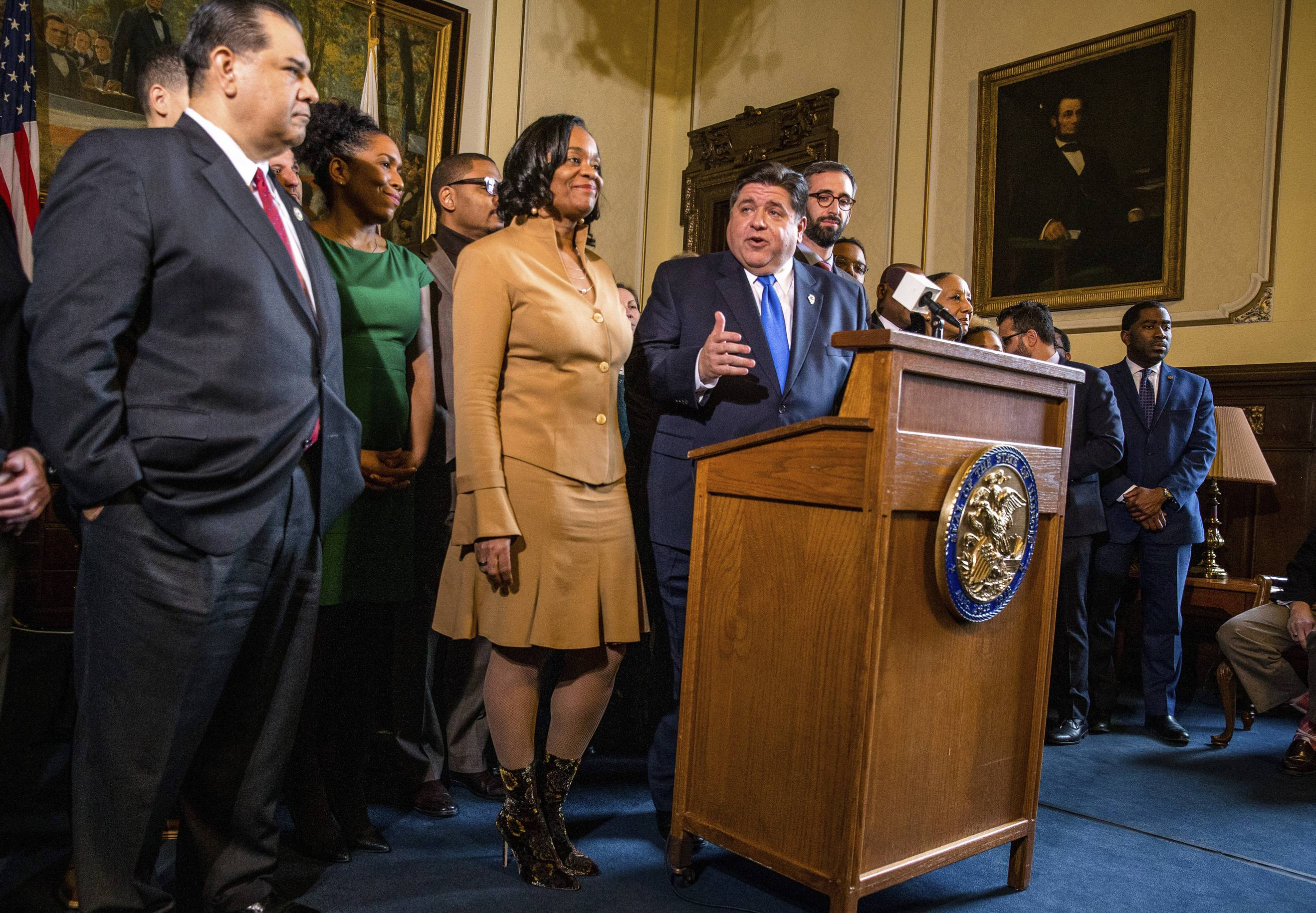 Illinois Gov. J.B. Pritzker gives his opening remarks along with Illinois State Sen. Kimberly Lightford, D-Maywood, left, on Senate Bill 1, a bill sponsored by Lightford to raise the state's minimum wage to $15 an hour by 2025, after it passed the Illinois Senate during a news conference in the governor's office at the Illinois state Capitol, Thursday in Springfield.