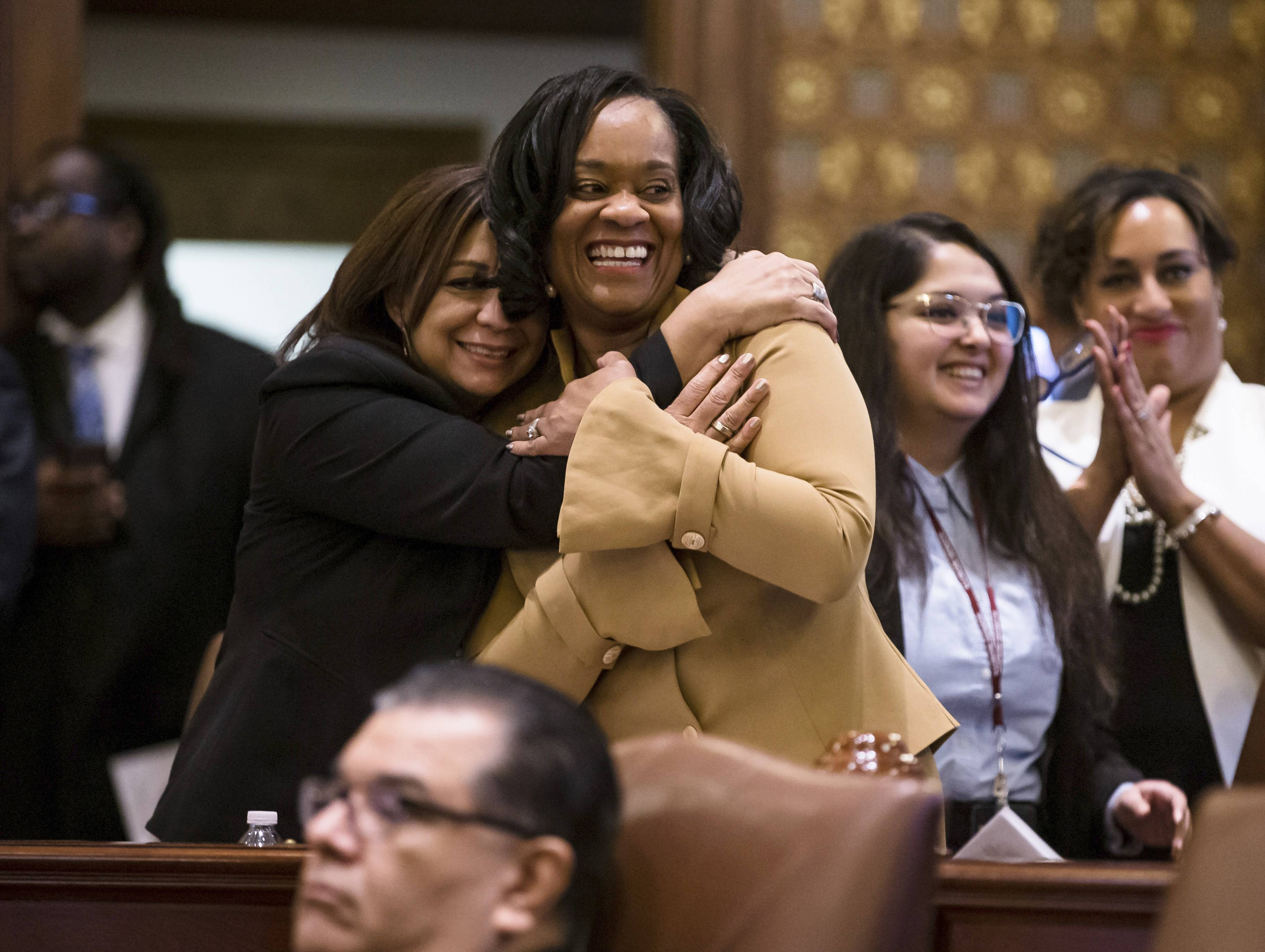 Illinois State Sen. Kimberly Lightford, D-Maywood, center, gets a hug from Illinois State Sen. Iris Martinez, D-Chicago, after Senate Bill 1, a bill sponsored by Lightford to raise the state's minimum wage to $15 an hour by 2025, passed the Senate on a vote of 39-18 at the Illinois state Capitol, Thursday in Springfield.