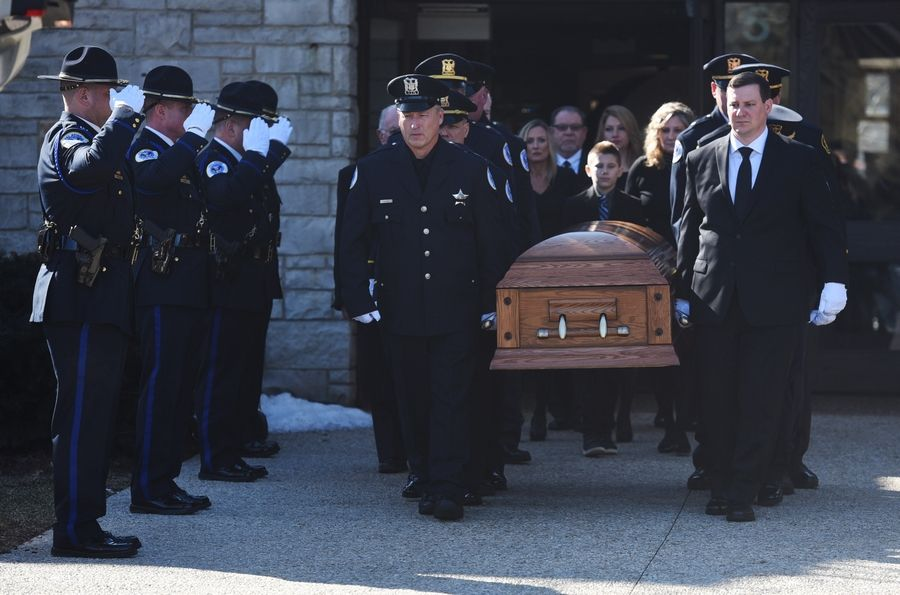 Pallbearers carry the casket of Palatine police officer Mark Dahlem, 48, of Cary during his funeral at Holy Family Church in Inverness Saturday. Dahlem died Tuesday after a battle with a rare and aggressive form of brain cancer.