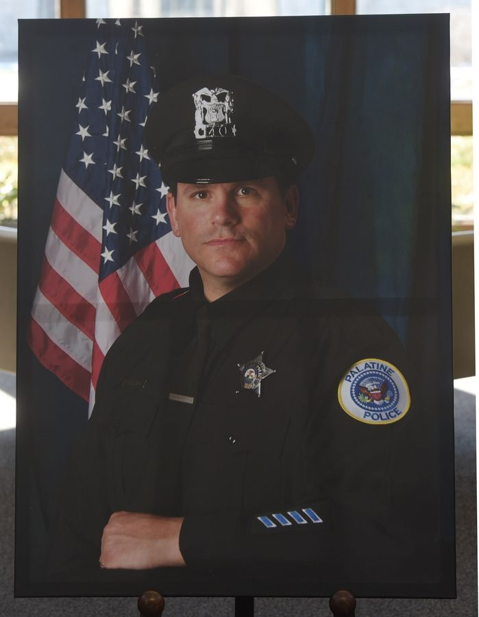A photo of Palatine police officer Mark Dahlem, 48, of Cary is displayed during his funeral at Holy Family Church in Inverness Saturday. Dahlem died Tuesday after a battle with a rare and aggressive form of brain cancer.
