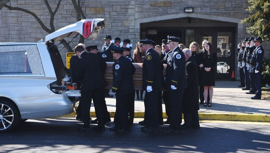 Pallbearers place the casket of Palatine police officer Mark Dahlem, 48, of Cary into the hearse during his funeral at Holy Family Church in Inverness Saturday. Dahlem died Tuesday after a battle with a rare and aggressive form of brain cancer.