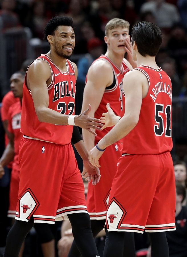 Chicago Bulls forward Otto Porter Jr., left, celebrates with guard Ryan Arcidiacono after scoring a basket against the Washington Wizards during the first half of an NBA basketball game Saturday, Feb. 9, 2019, in Chicago.
