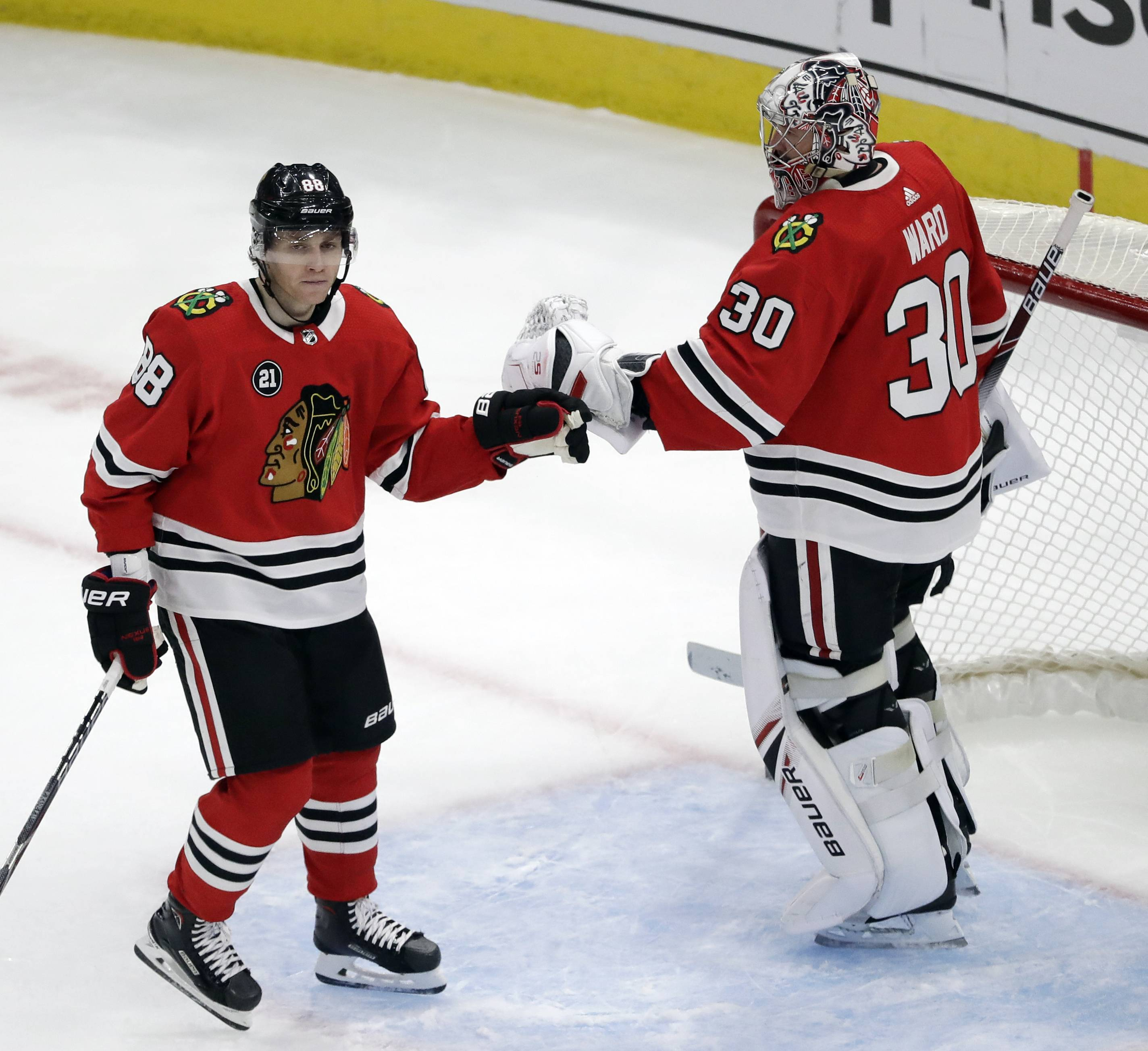 Chicago Blackhawks right wing Patrick Kane, left, celebrates with goalie Cam Ward after scoring a goal against the Detroit Red Wings during the third period of an NHL hockey game Sunday, Feb. 10, 2019, in Chicago. The Blackhawks won 5-2.