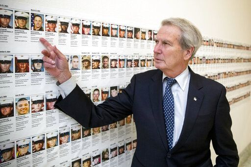 FILE - In this Oct. 25, 2017, file photo, U.S. Rep. Walter Jones, R-N.C., points at a photograph of Marine Sgt. Michael Edward Bits of Ventura, Calif., the first military funeral he and his wife attended, and one of the many pictures of soldiers killed this century based at Camp Lejeune, N.C., along a hallway leading to his office on Capitol Hill in Washington. Jones, a once-fervent supporter of the 2003 invasion of Iraq who later became an equally outspoken Republican critic of the war, died Sunday, Feb. 10, 2019, his 76th birthday.