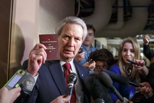FILE - In this Thursday, Feb. 26, 2015, file photo, U.S. Rep. Walter B. Jones Jr., R-N.C., holds up a copy of the Constitution while talking to reporters as House Republicans emerge from a closed-door meeting on how to deal with the impasse over the Homeland Security budget, at the Capitol in Washington. Jones, a once-fervent supporter of the 2003 invasion of Iraq who later became an equally outspoken Republican critic of the war, died Sunday, Feb. 10, 2019, his 76th birthday.