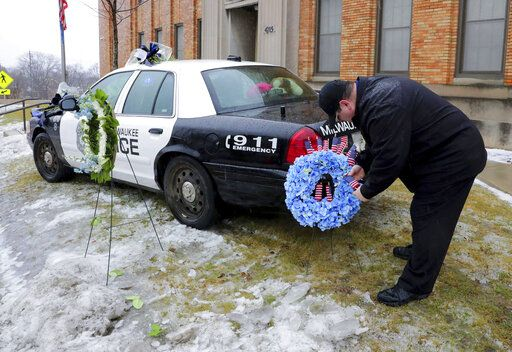 Timothy Nelson, of Oak Creek, Wis., places small flags in a bouquet near a squad car adorned with flowers as a memorial for fallen Milwaukee Police Officer Matthew Rittner at the Neighborhood Task Force police building in Milwaukee on Thursday, Feb. 7, 2019.  Police are collecting evidence at a Milwaukee home where a police officer was fatally shot while serving a warrant. Investigators say 35-year-old Officer Matthew Rittner was killed Wednesday as members of Milwaukee's Tactical Enforcement Unit served the warrant on someone suspected of illegally selling firearms and drugs. (Mike De Sisti/Milwaukee Journal-Sentinel via AP)