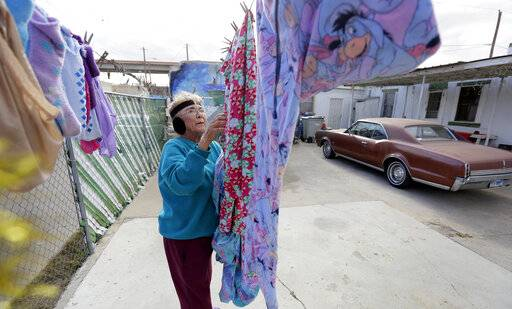 In this Tuesday, Jan. 22, 2019, photo, Mickie Subia gathers her laundry at her home in El Paso, Texas. Subia lives less than a block away from a border barrier that runs along the Texas-Mexico border in El Paso.