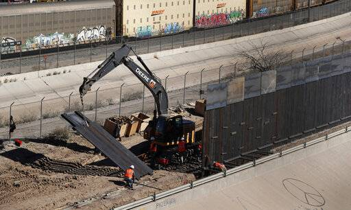 In this Tuesday, Jan. 22, 2019, photo, workers place sections of metal wall as a new barrier is built along the Texas-Mexico border near downtown El Paso. Such barriers have been a part of El Paso for decades and are currently being expanded, even as the fight over President Donald Trump's desire to wall off the entire U.S.-Mexico border.