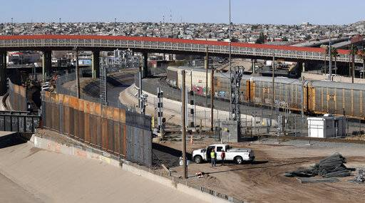 In this Tuesday, Jan. 22, 2019, photo, a new barrier is built along the Texas-Mexico border near downtown El Paso. Such barriers have been a part of El Paso for decades and are currently being expanded, even as the fight over President Donald Trump's desire to wall off the entire U.S.-Mexico border.