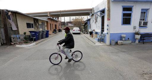 In this Monday, Jan. 21, 2019, photo, Mario Silva leaves his home on a bike in El Paso, Texas. Silva's home backs up to a border barrier that runs along the Texas-Mexico border in El Paso.n