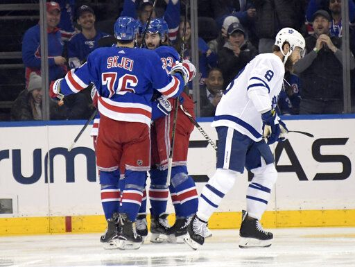 New York Rangers center Mika Zibanejad (93) celebrates with Brady Skjei (76) as Toronto Maple Leafs defenseman Jake Muzzin (8) reacts after Zibanejad scored during the first period of an NHL hockey game Sunday, Feb. 10, 2019, at Madison Square Garden in New York.