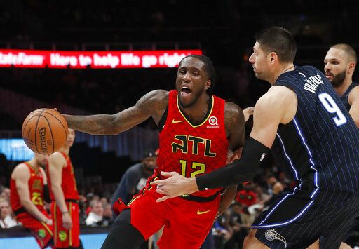 Atlanta Hawks forward Taurean Prince (12) drives against Orlando Magic center Nikola Vucevic (9) during the first half of an NBA basketball game Sunday, Feb. 10, 2019, in Atlanta.