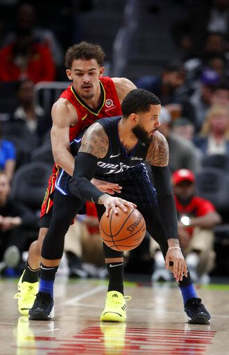 Orlando Magic guard D.J. Augustin (14) is defended by Atlanta Hawks guard Trae Young (11) during the first half of an NBA basketball game Sunday, Feb. 10, 2019, in Atlanta.