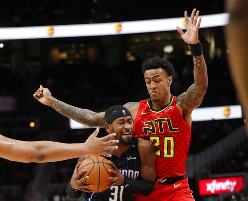 Orlando Magic guard Terrence Ross (31) tries to get around Atlanta Hawks forward John Collins (20) 'during the second half of an NBA basketball game Sunday, Feb. 10, 2019, in Atlanta. Orlando won 124-108.