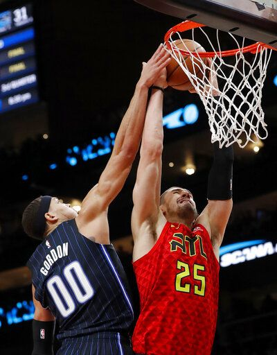 Atlanta Hawks center Alex Len (25) goes up for a basket as Orlando Magic forward Aaron Gordon (00) defends during the first half of an NBA basketball game Sunday, Feb. 10, 2019, in Atlanta.