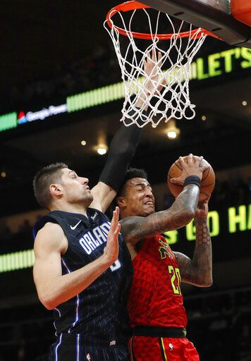 Atlanta Hawks forward John Collins (20) goes up for a basket as Orlando Magic center Nikola Vucevic (9) defends during the first half of an NBA basketball game Sunday, Feb. 10, 2019, in Atlanta.