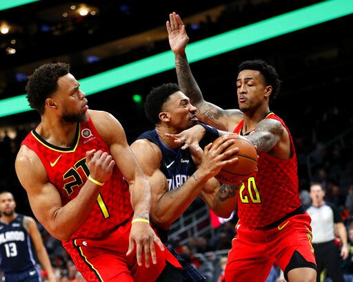 Orlando Magic center Khem Birch (24) is defended by Atlanta Hawks John Collins (20) and Justin Anderson (1) as he goes up for a shot during the second half of an NBA basketball game Sunday, Feb. 10, 2019, in Atlanta. Orlando won 124-108.